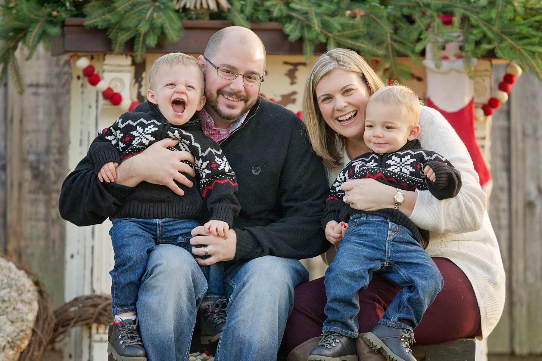 mom, dad and twin boys pose in front of holiday mantel