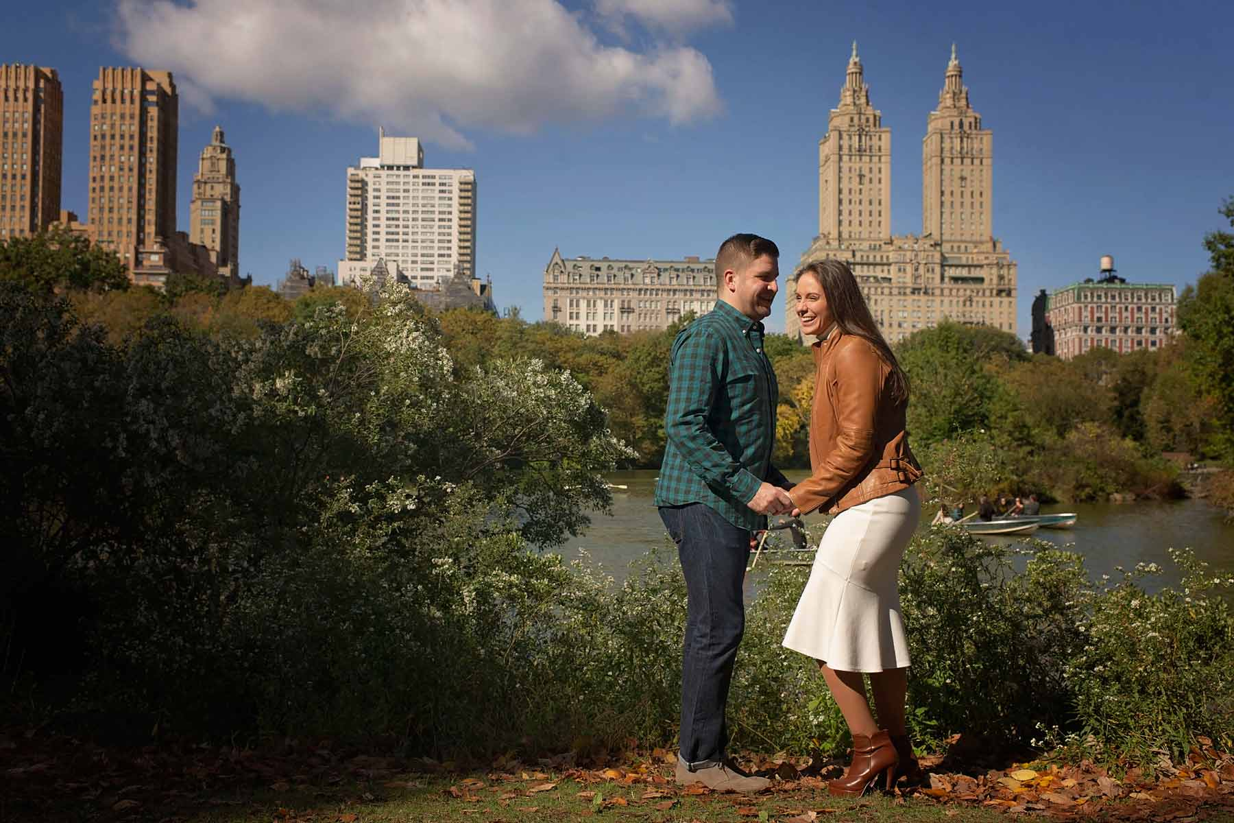 girl laughing with fiance in front of new york city skyline in central park
