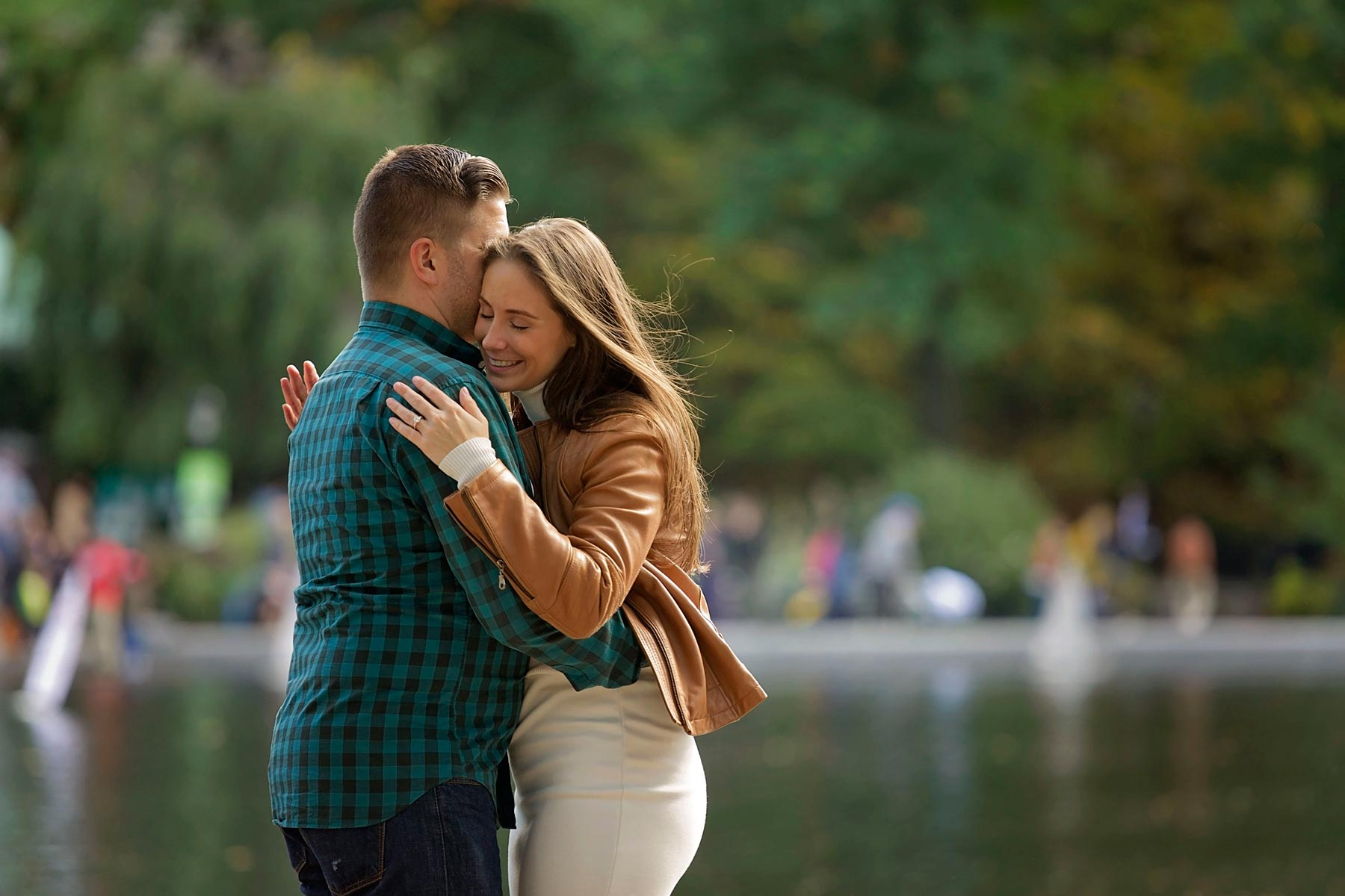 couple hugging at conservatory water in central park in new york city