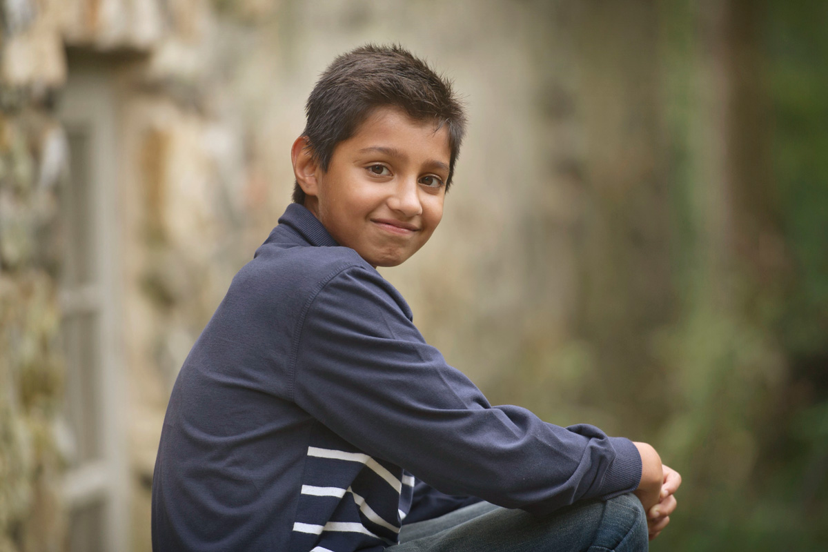 Boy posing on step with arms crossed over knee at Brandywine River Museum