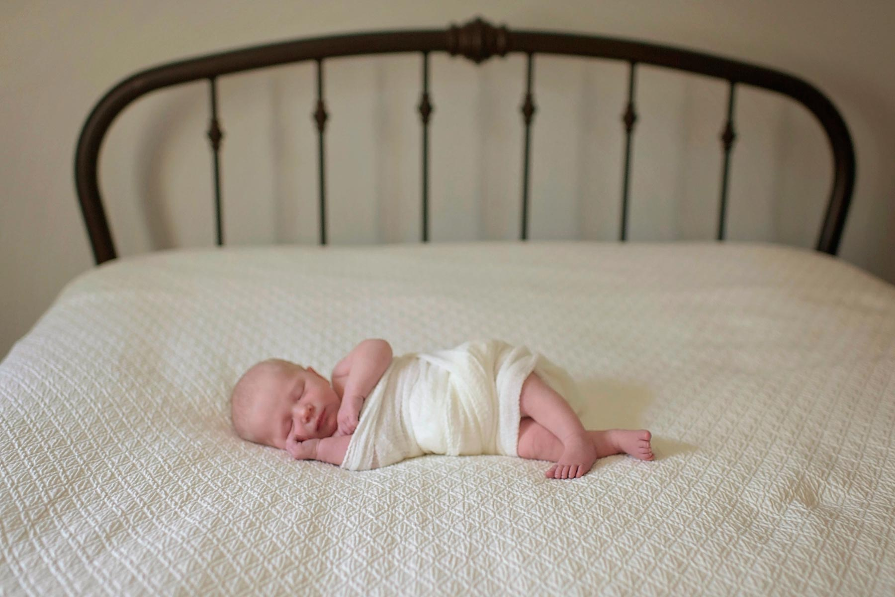 newborn baby swaddled on a bed