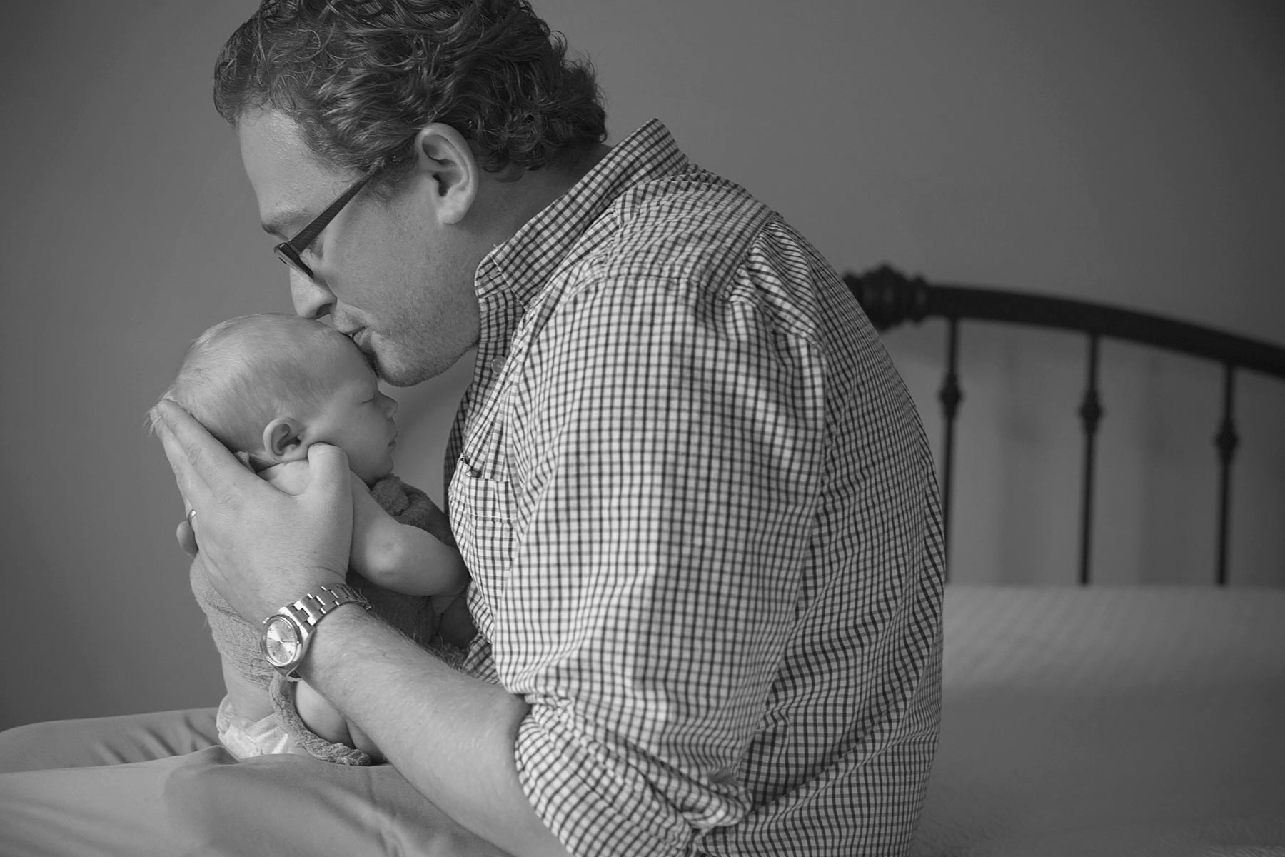 new dad holding and kissing baby girl