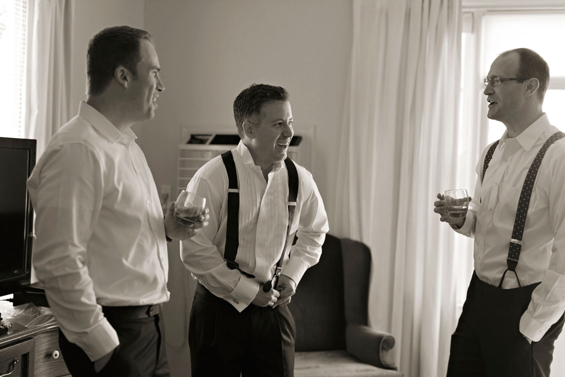 groom getting dressed with groomsmen in his hotel room