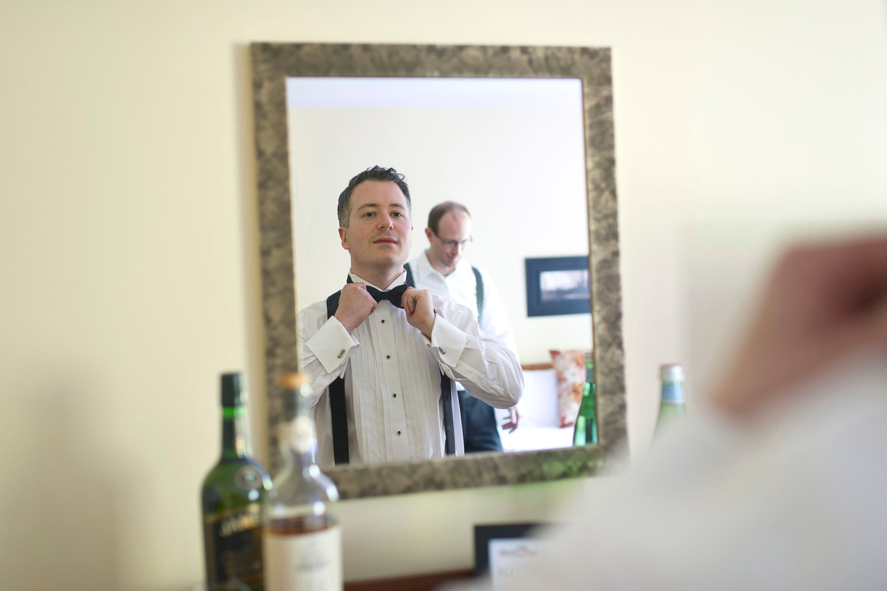 Groom tying his bow tie getting ready for wedding