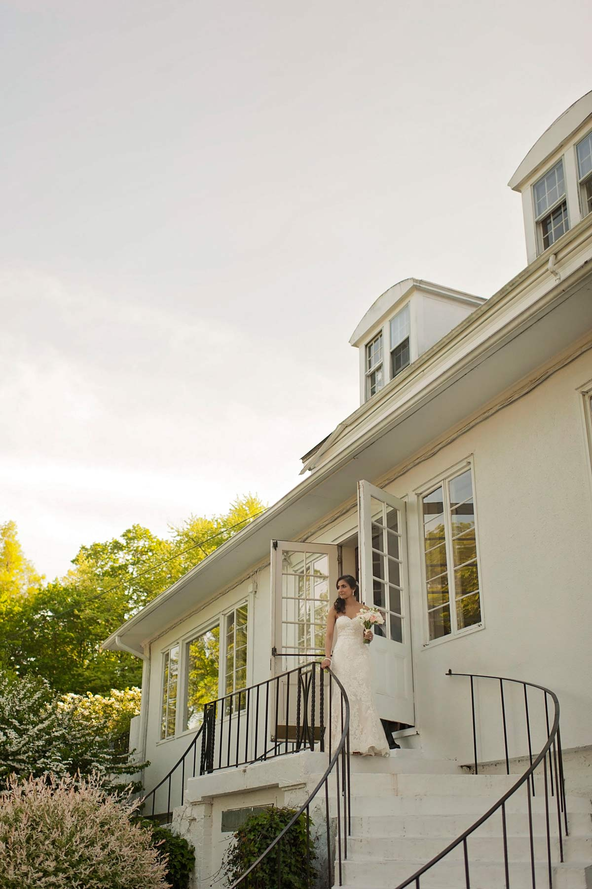 bride descending the stairs at crabtree's kittle house in chappaqua