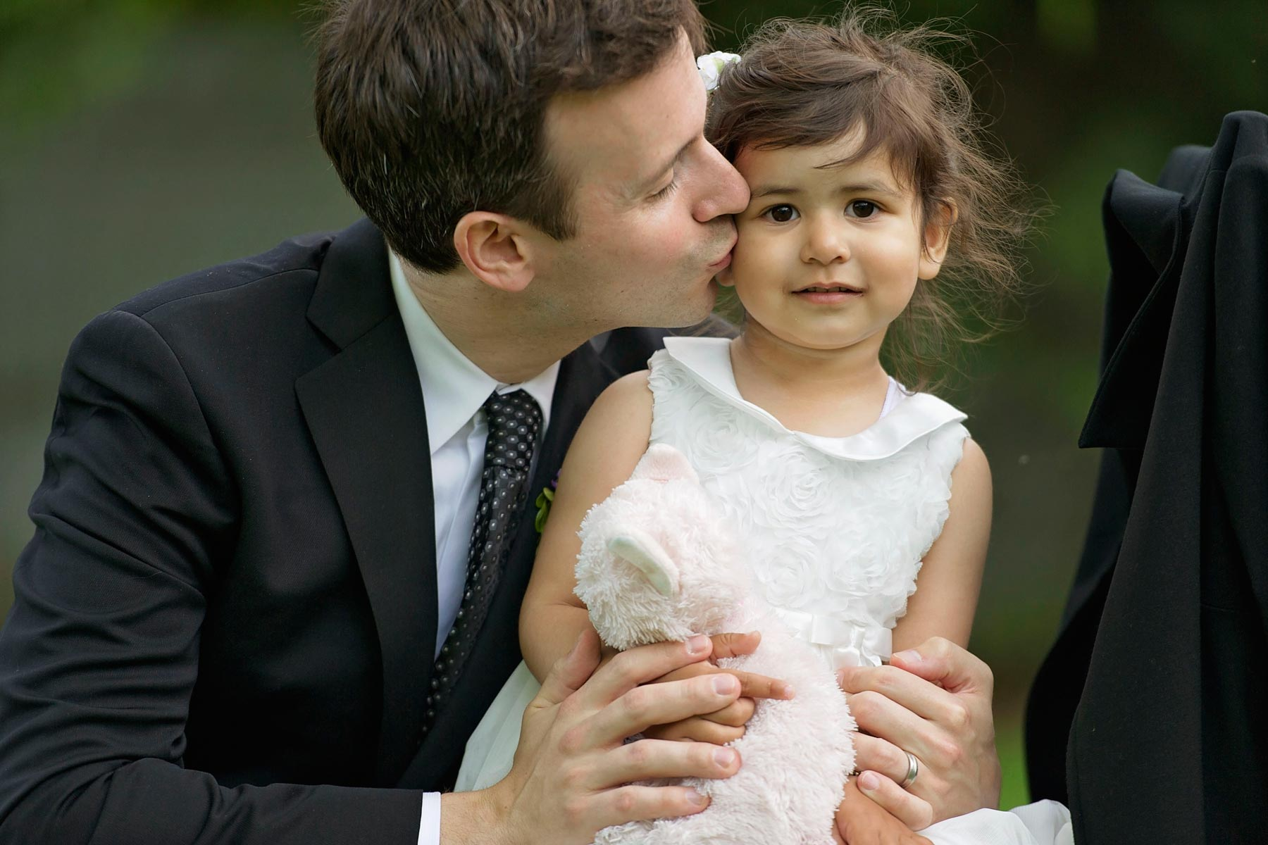 groomsman kissing his daughter, the flower girl