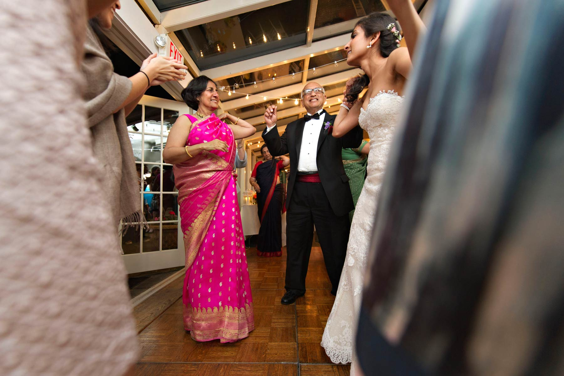 bride dances with her parents at wedding reception