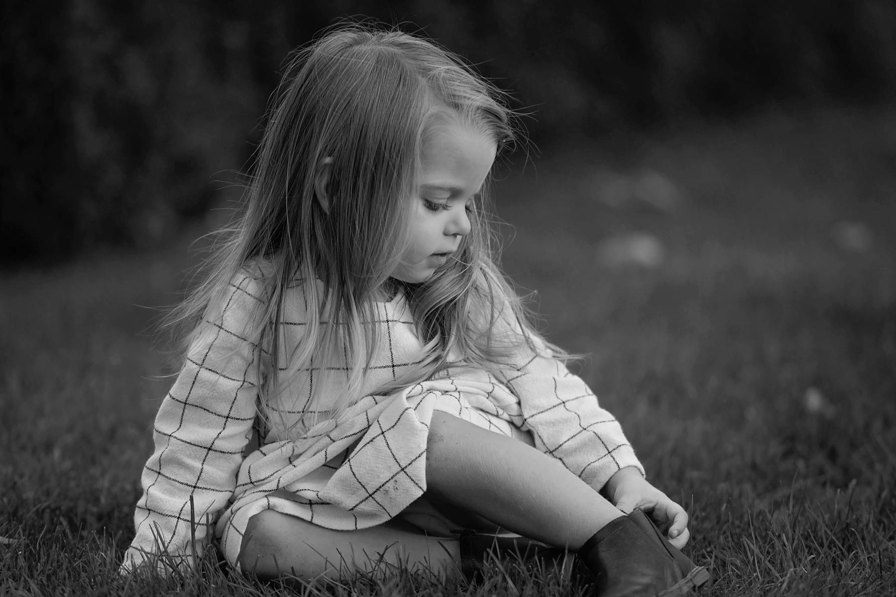 black and white image of 2 year old girl sitting and touching her shoe