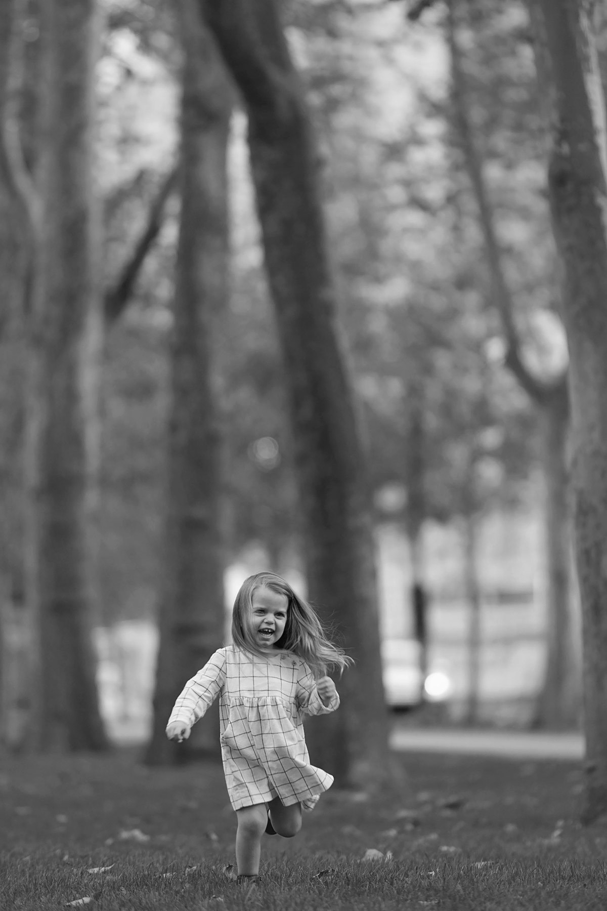 black and white of little girl running through two rows of trees outside the rodin museum