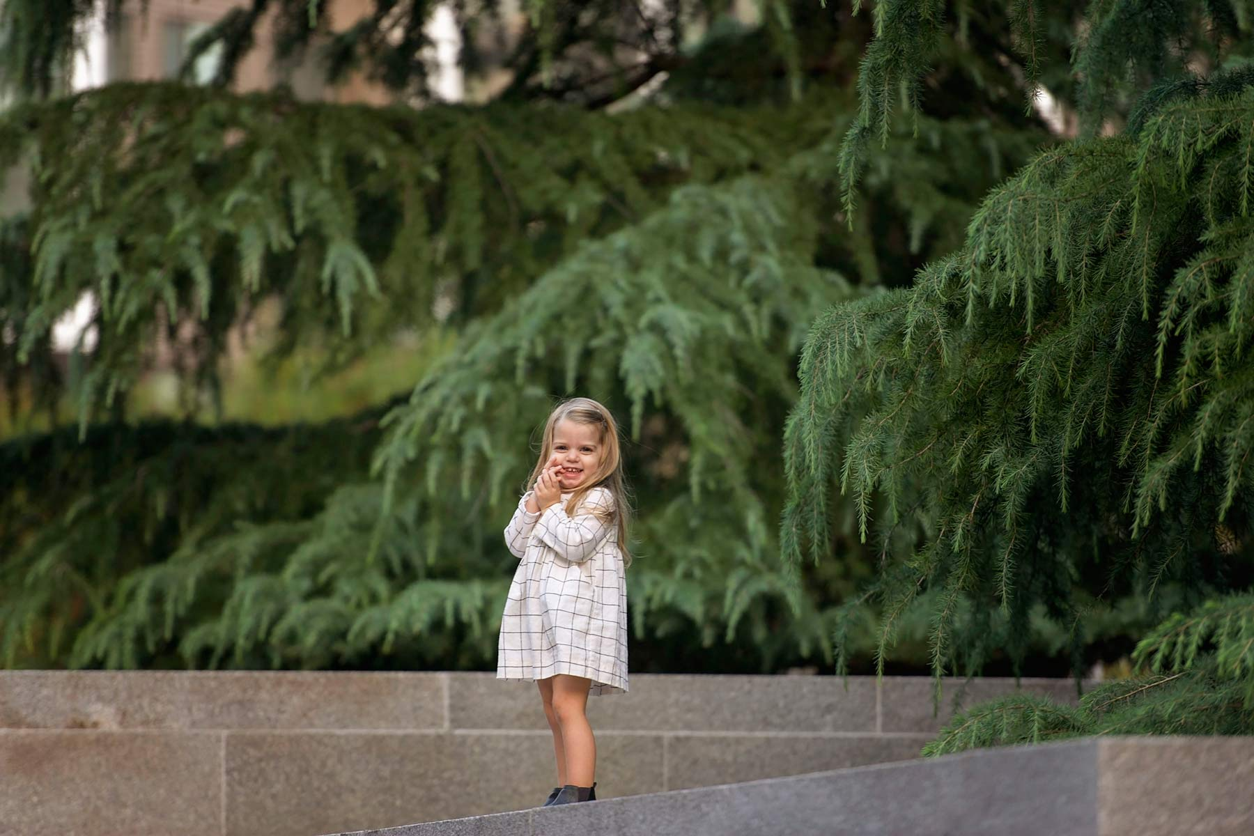 little girl in white dress and boots standing amidst evergreen trees
