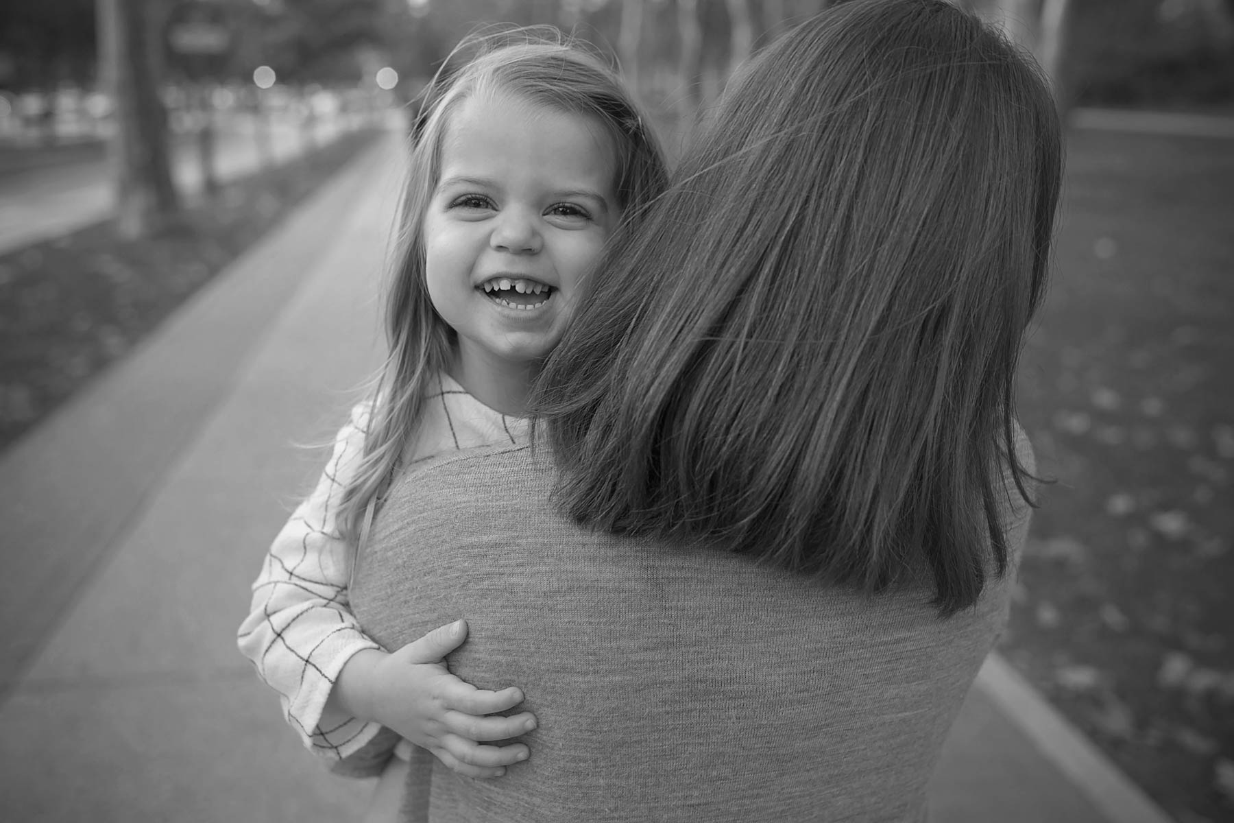black and white of 2 year old being held by mother and walking looking over her shoulder
