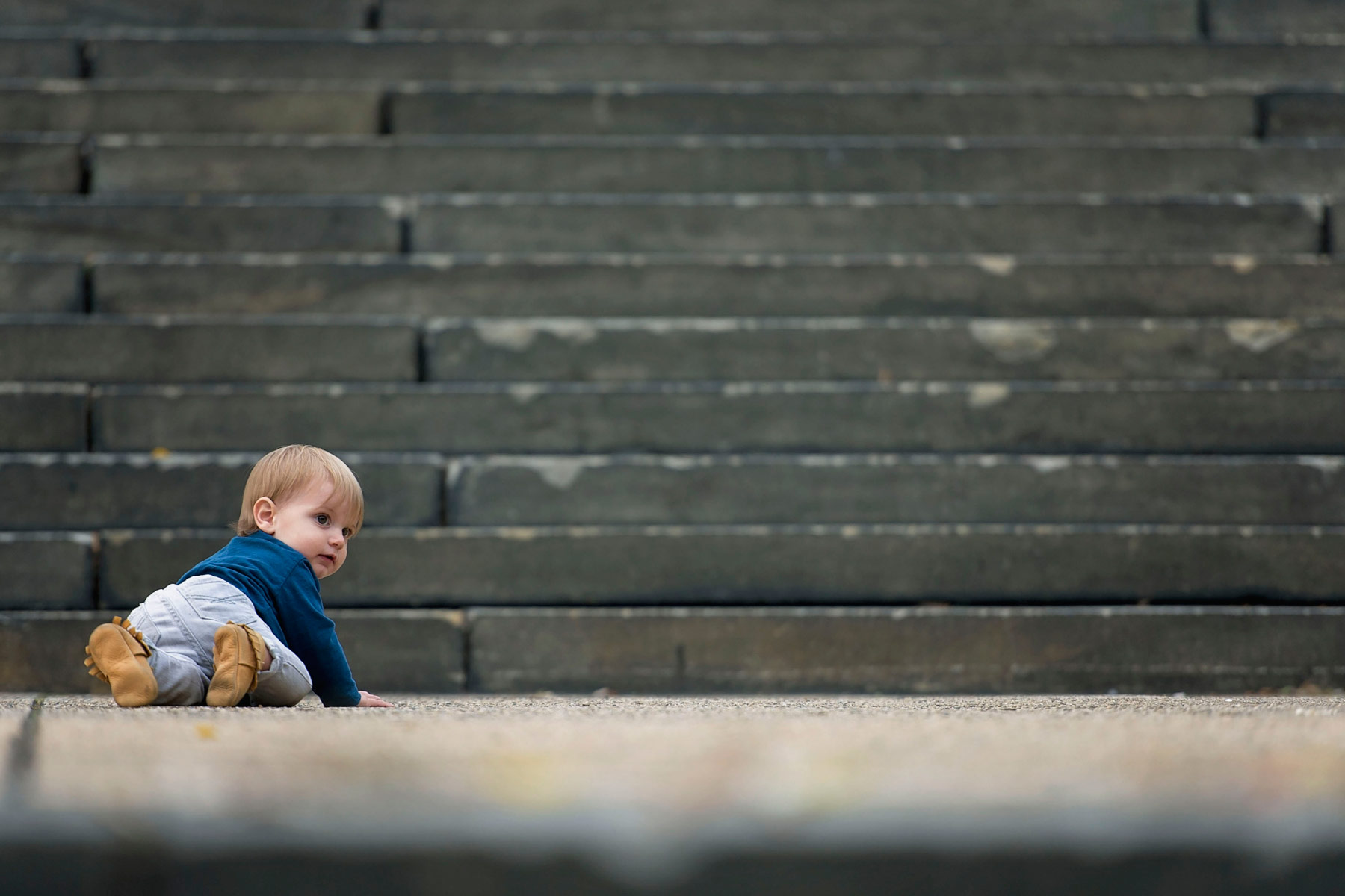 one year old boy at the bottom of a big set of stairs outside the philadelphia art museum looking back at the camera