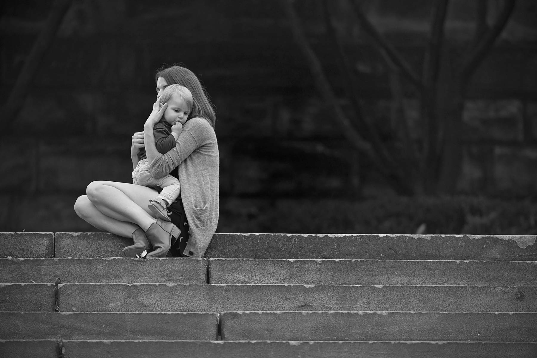 black and white of a mother comforting son at the top of a staircase outside the philadelphia art museum