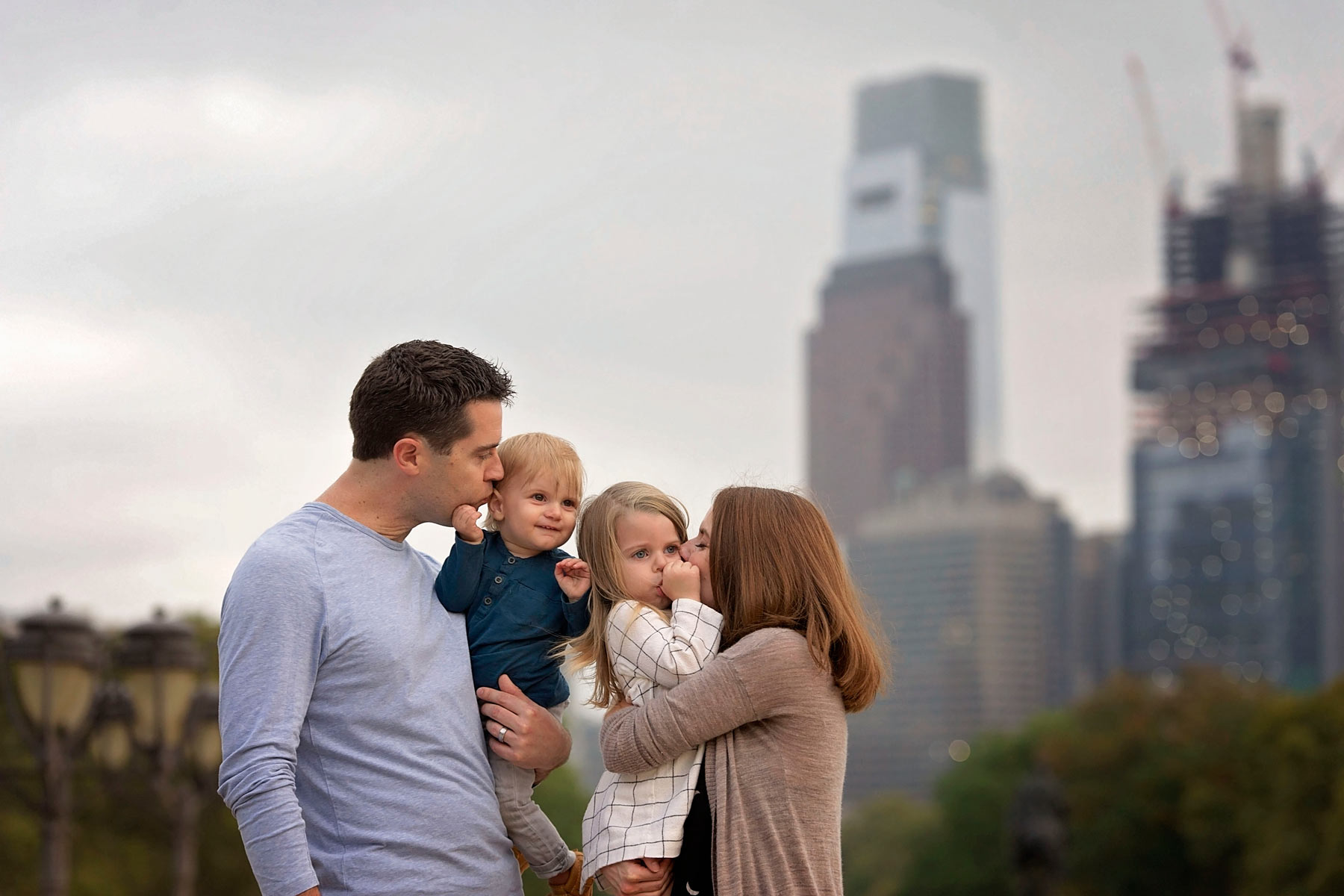 family of four on the steps of the philadelphia art museum with the skyline in the background