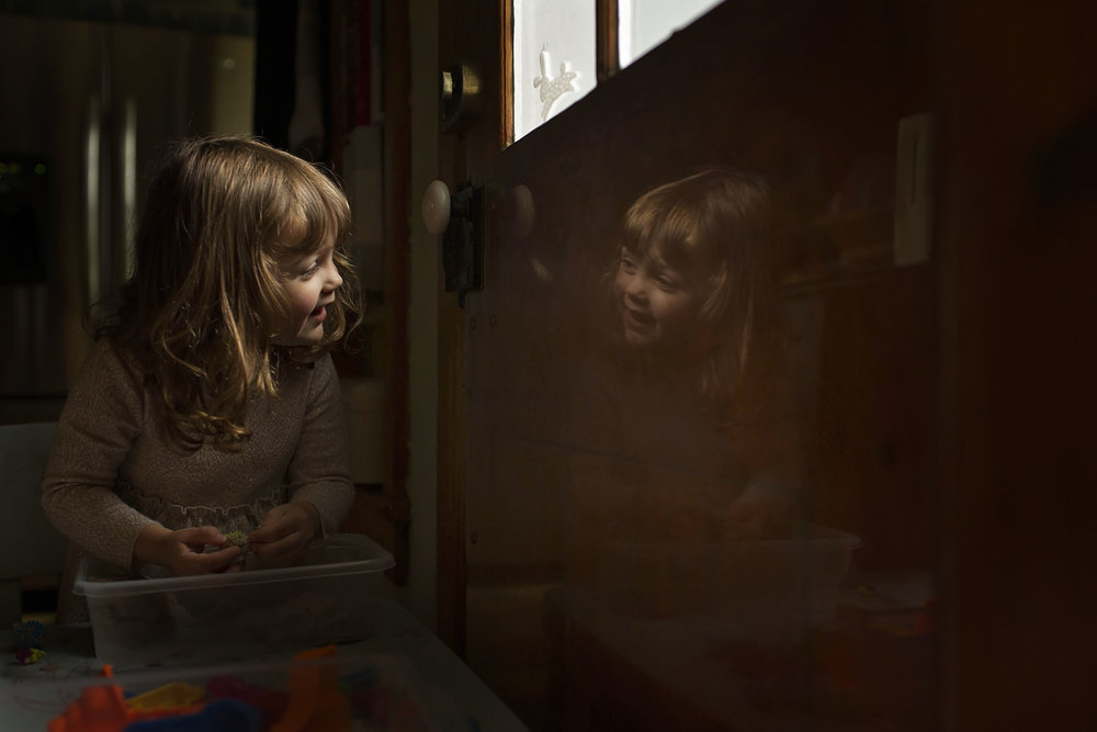 Little girl looking at reflection