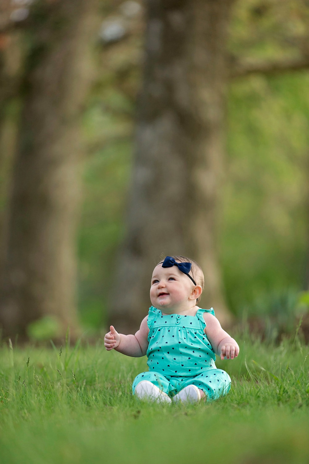 baby girl laughs while sitting in wooded area