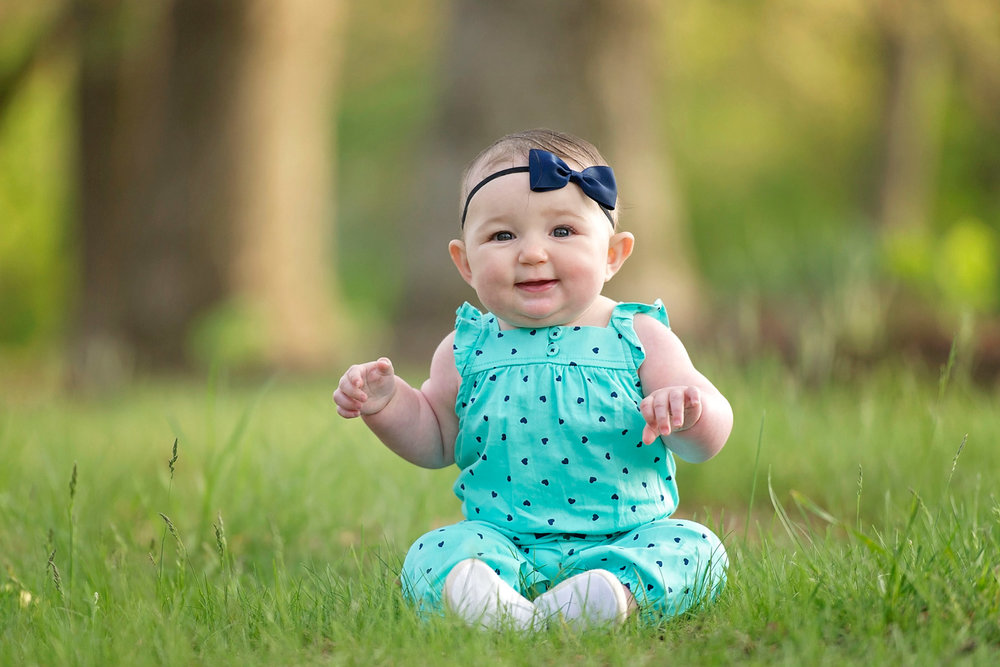 six month old baby girl smiles while sitting in wooded area wearing blue headband