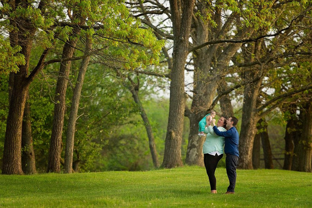 mom holds baby up in the air with dad standing close behind in a wooded area