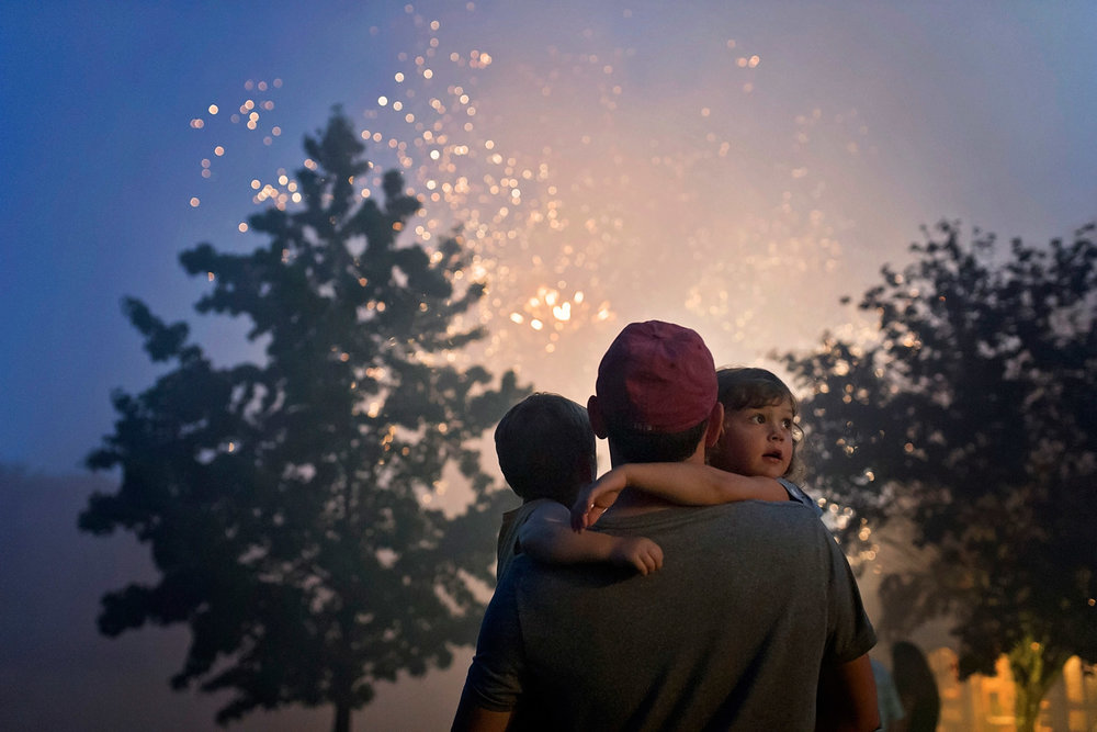 Father holdingn two children standing in front of fireworks display