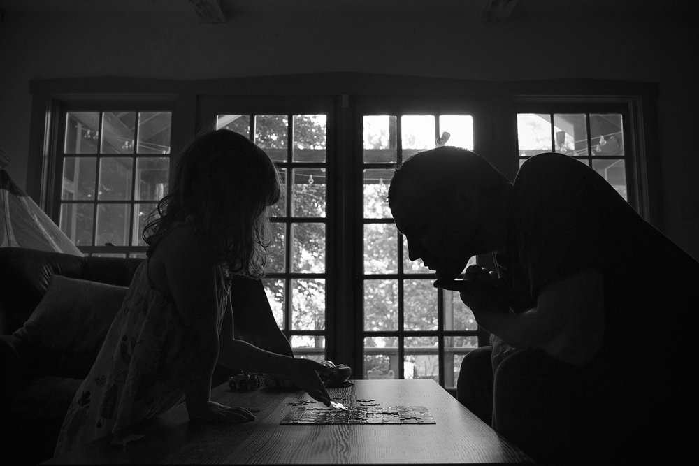 silhouette of father and daughter doing a puzzle together