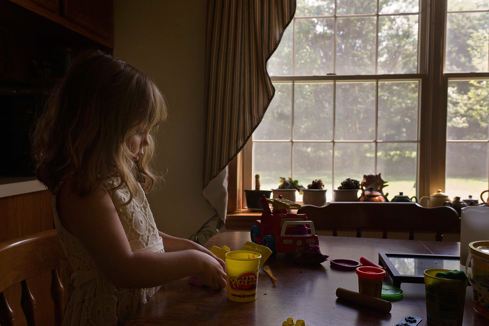 3 year old girl playing with play doh at table in front of window