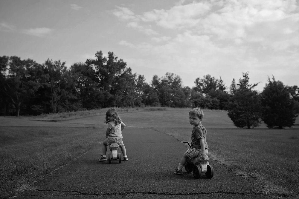 black and white photo of toddler girl and boy sitting on their bikes looking over their shoulder at the camera