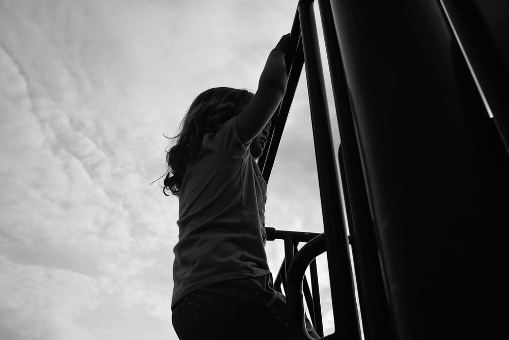 black and white photo of girl hanging on a bar at the playground