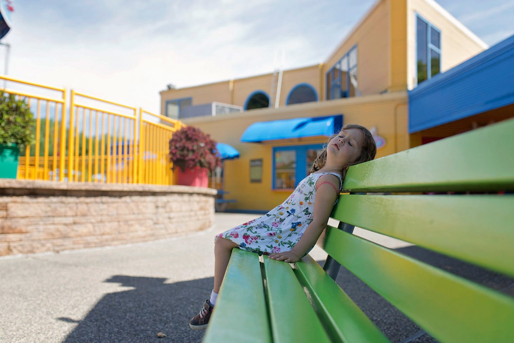 little girl relaxes on bench with eyes closed at sesame place