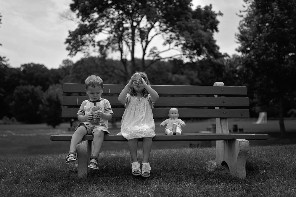 toddler brother and sister sit on park bench with baby doll drinking from sippy cups