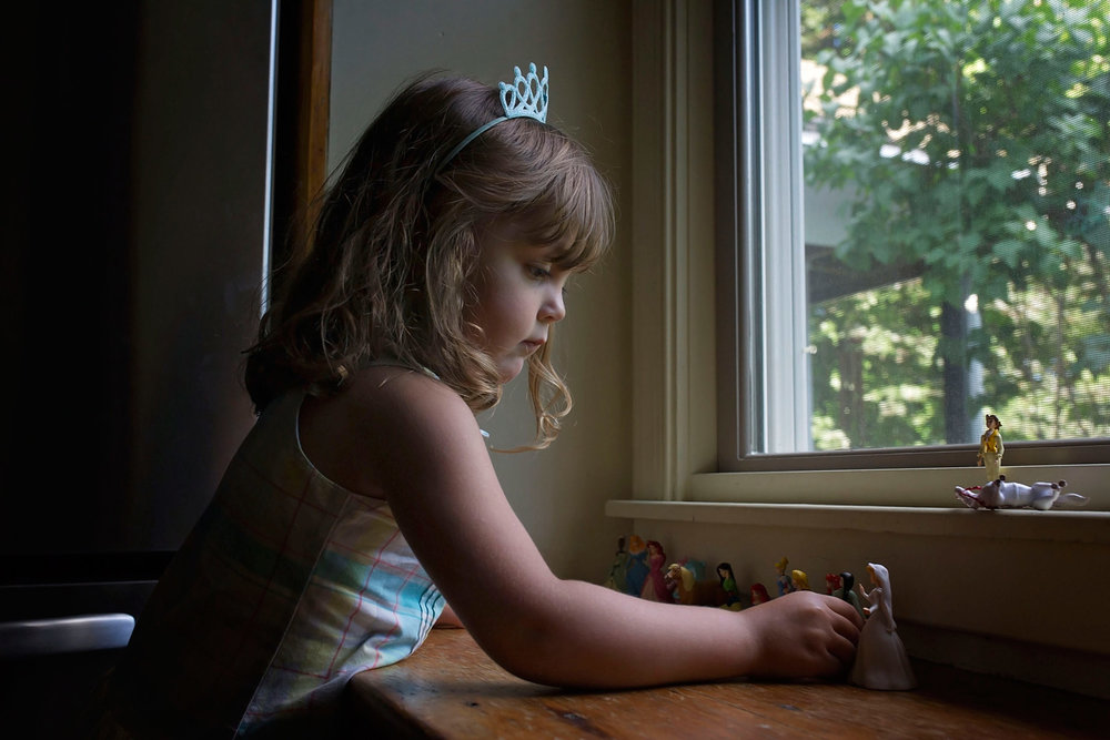 4 year old plays with princess figurines by window while wearing a crown