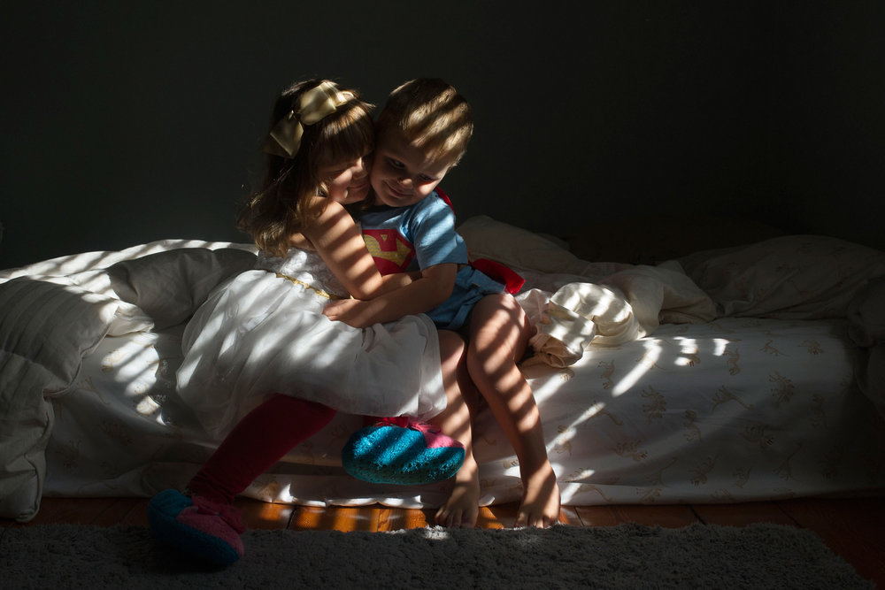 toddler brother and sister hug in the light and shadows of the blinds