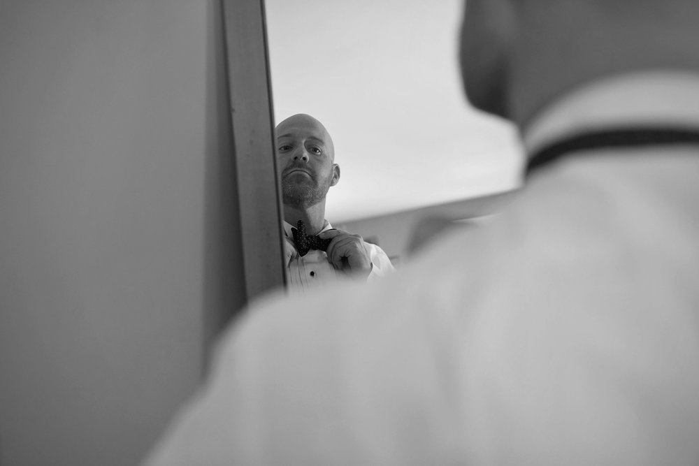 groom adjusts his bowtie in the mirror