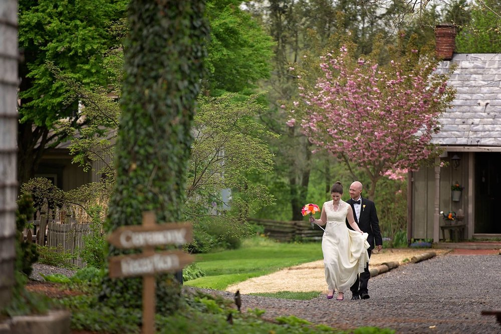 bride and groom make their way down a path