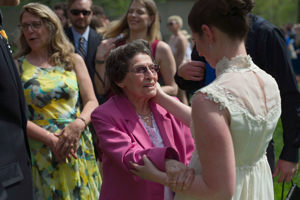 grandmother looks at bride as bride touches her cheek