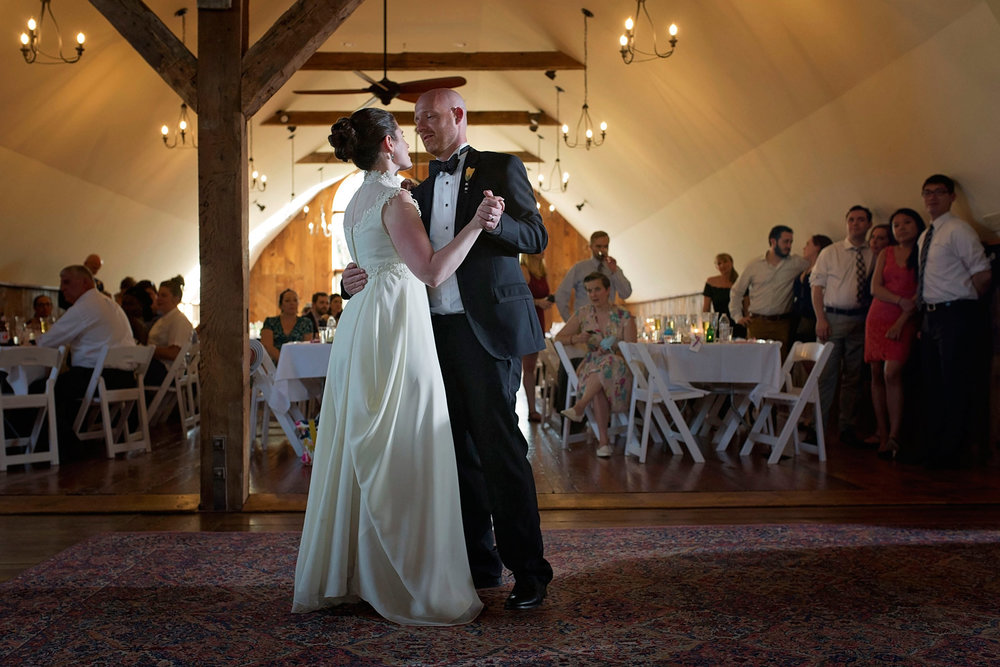 bride and groom share their first dance in the barn