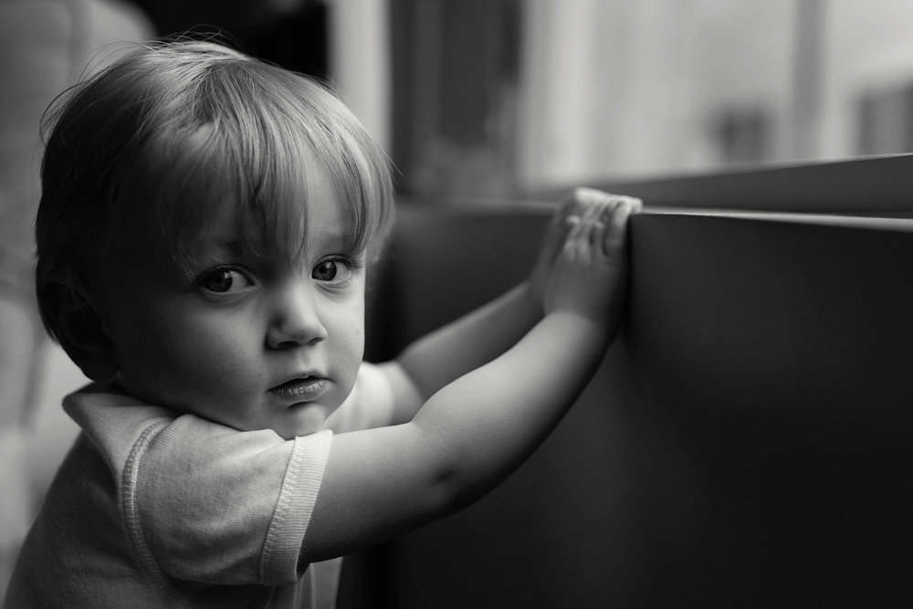 black_and_white_image_of_toddler_boy_looking_at_camera_by_window.jpg