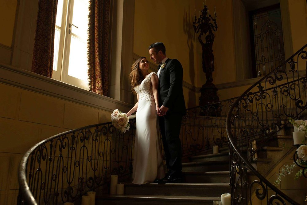 10_Bride_and_groom_on_stairway_Oheka_Castle.jpg