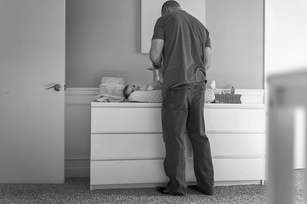 dad changes baby's diaper on changing table