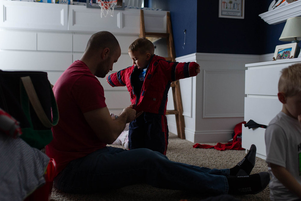dad zips son's coat to get ready to go outside