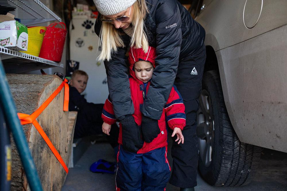 mom helps son unzip his coat in the garage