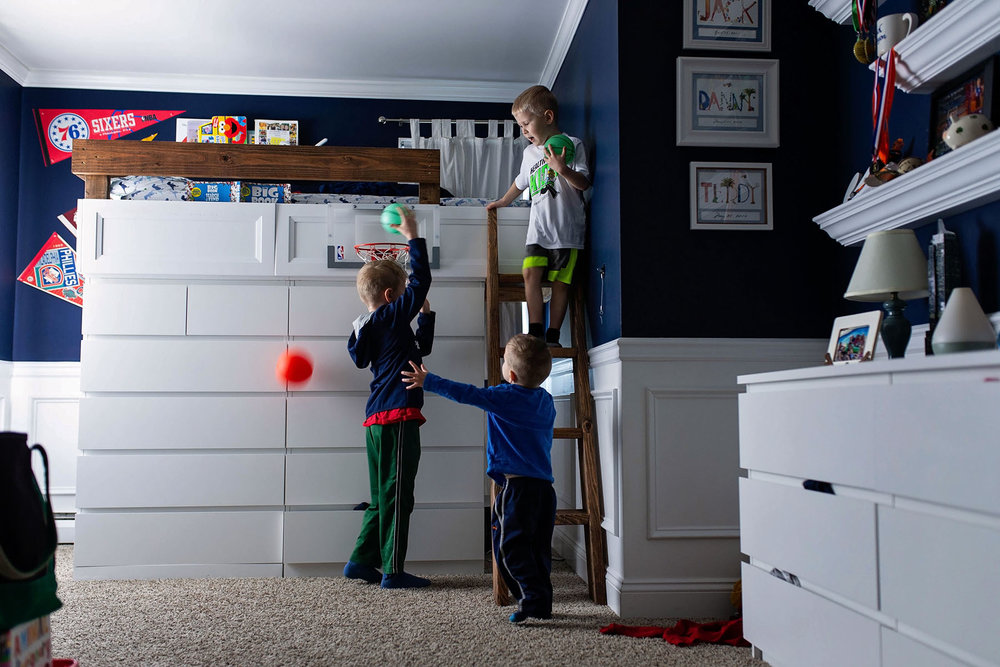 three brothers play basketball in their room