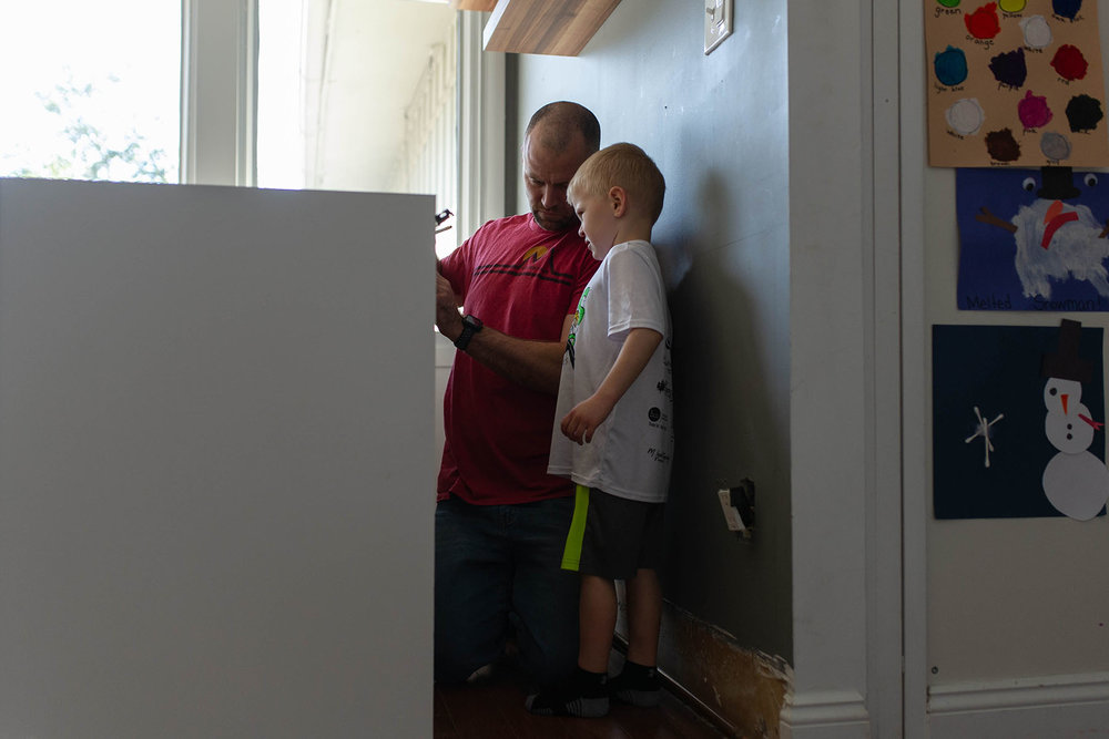 boy helps his dad measure for kitchen remodeling