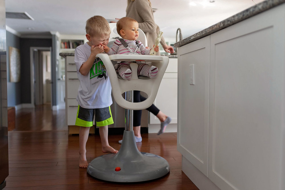 brother plays with baby sister in high chair