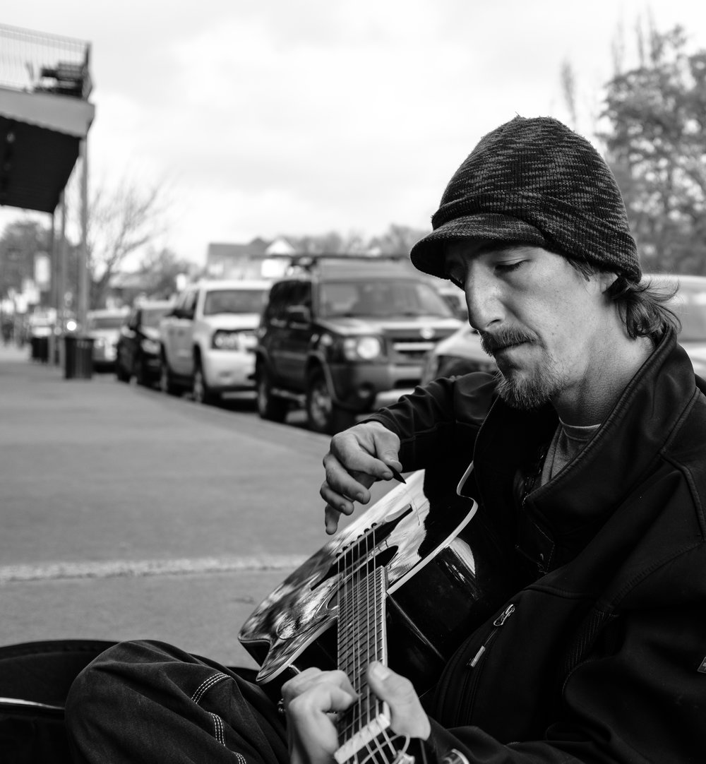 """I sat down to listen to this guy's music. The lyrics were heart-wrenching and beautiful. He told me he'd written it when he was 14, after witnessing his dad abuse his mom for the first time. """"This thing right here is my baby"""" he said slapping his guitar, """"it's a part of me, because it got me through all of that."""" He's got skin cancer on the back of his knee, and due to lack of available medical care it has spread to his bone. At the time of writing, he's waiting on his medicaid to go through."""