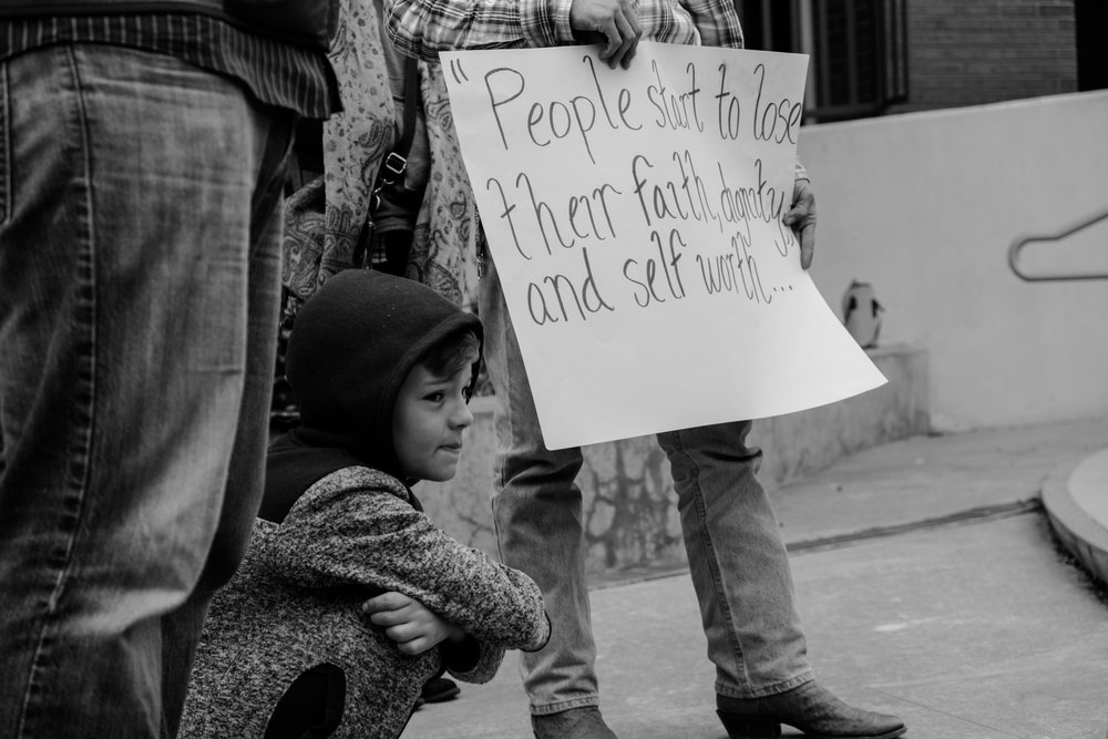 A young boy squats next to a marcher as the mayor speaks.