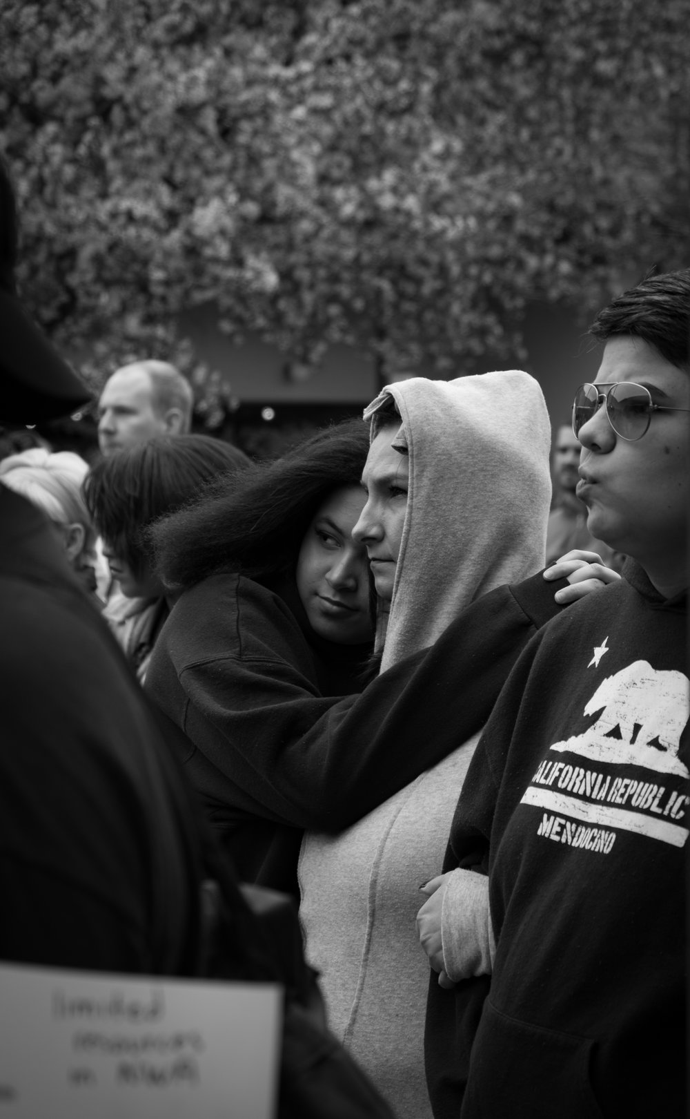 Two women embrace in a moment of compassion as a homeless man stands in front of the crowd to tell his story.