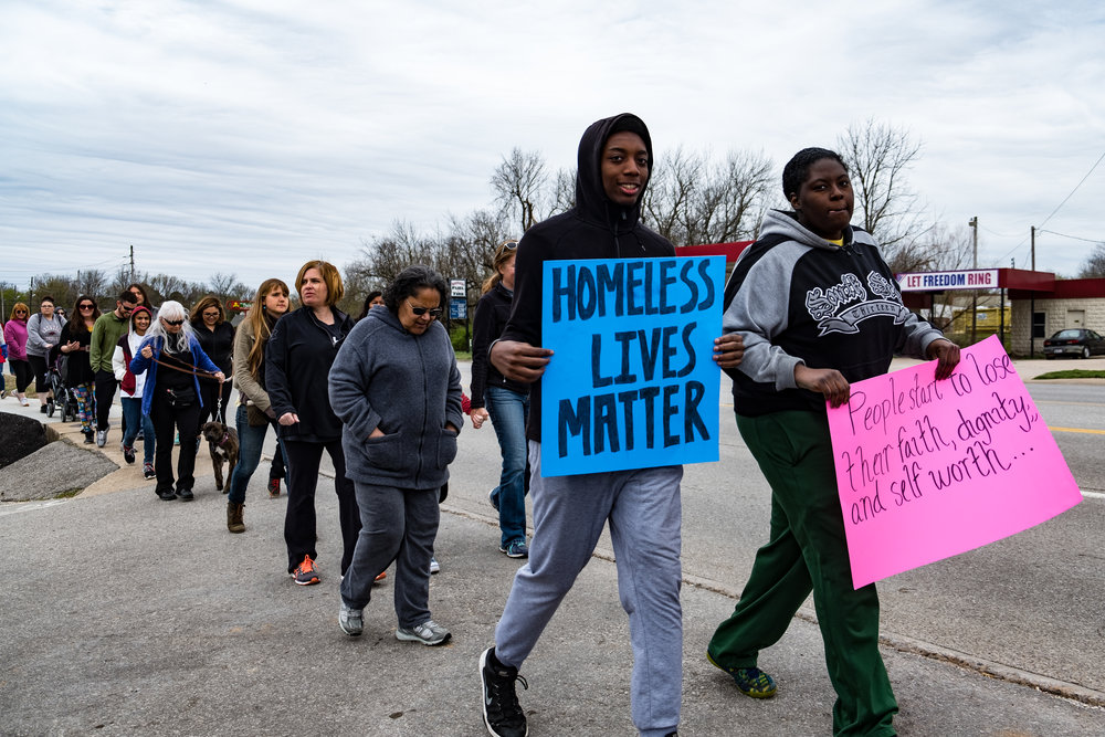 "A young man shows a ""homeless lives matter"" sign halfway through the march."