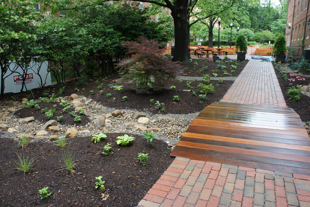 Installed design - stormwater channel with footbridge and walkway with permeable brick paving.
