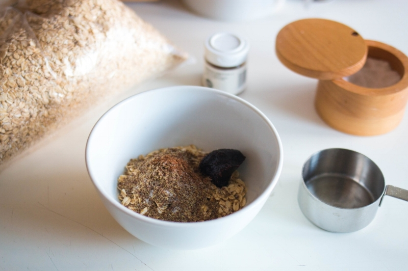 Old-fashioned oats, flax, cinnamon, sea salt, and date paste in a bowl before adding liquid.