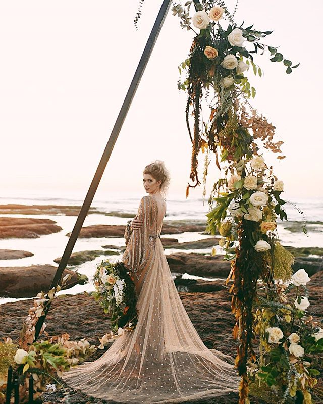 The Sirens were sea-nymphs who lured sailors to their death with a bewitching song.  Florals: @thefloralcraft, Arch: @ccvintagerentals, Planning: @urbanshindigs, H/MU: @erin_scissorhands, Dress: @thedresstheorysandiego, Photo: @thisradlove